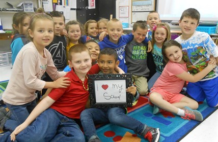 "Elementary students holding an ""I love my school"" sign"
