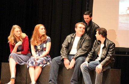 "Scene from ""The Outsiders"" — Five actors sit on edge of stage. Wearing leather jackets."