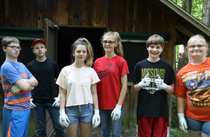 Six students stand outside a rustic cabin.